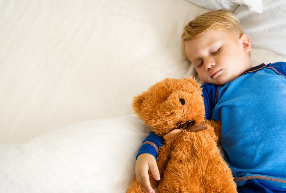 boy sleeping with teddy