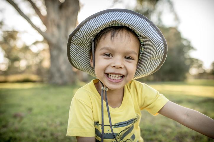 Cute mixed race Asian Caucasian boy plays in a park