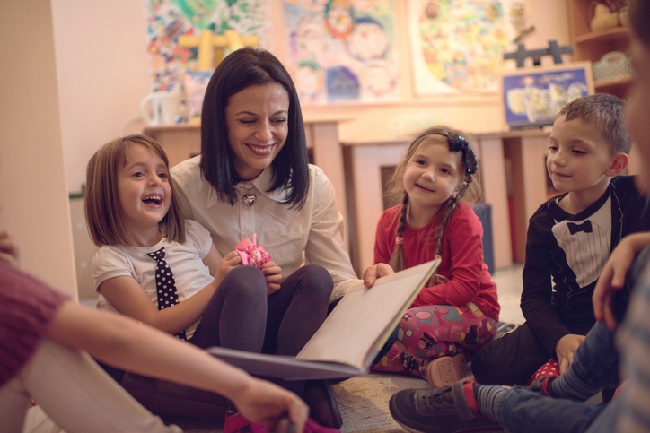 Happy preschool teacher telling stories to group of kids.