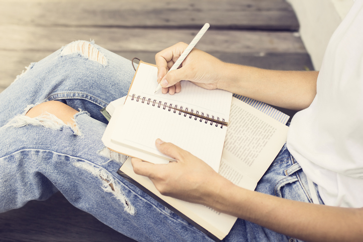 Girl sitting on floor and wrote in a notebook