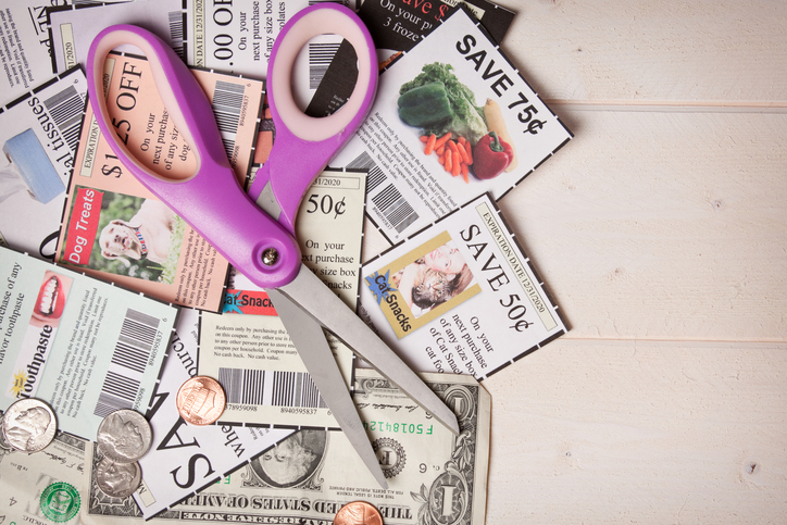 A pair of scissors laying on top of coupons and money. (note: coupons were created by photographer with own photographs)