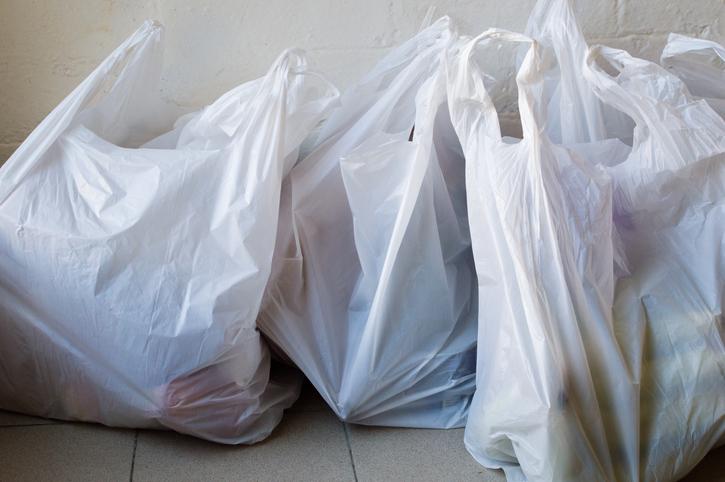 Full frame view of full plastic shopping bags on tiled floor