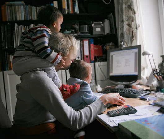 Mother working at home on the pc, with her children doing multi-tasking work.