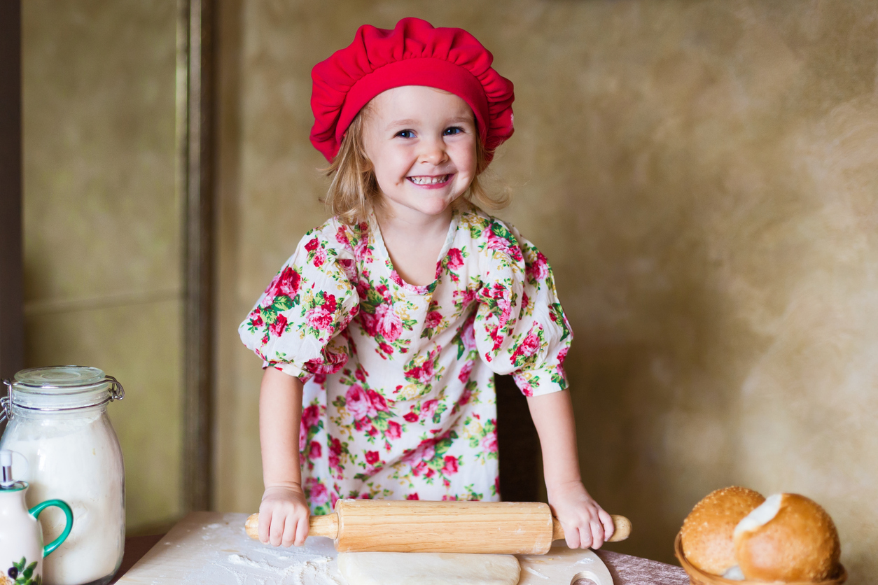 beautiful smiling little blonde girl in red beret with french bread