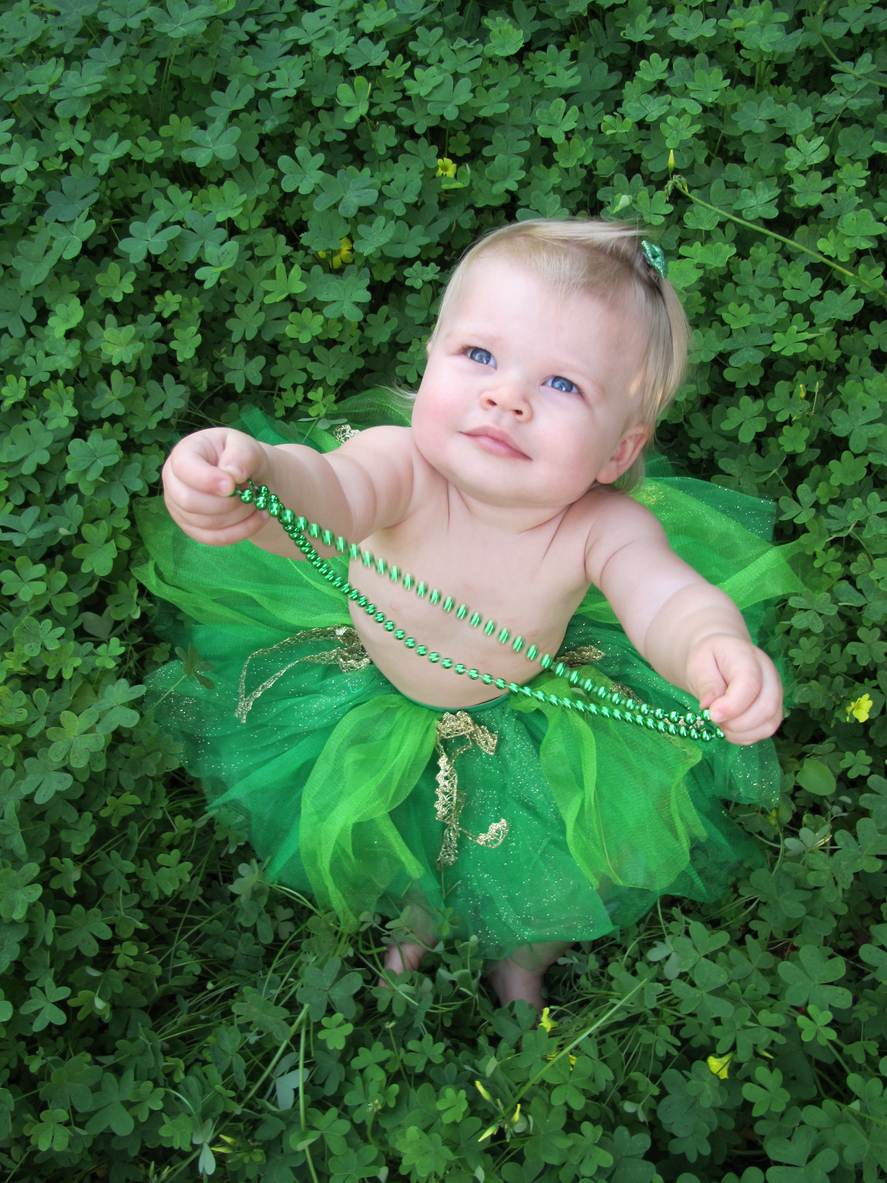 A cute baby girl in a green tutu plays with her green necklace while sitting in a patch of clovers for St. Patrick's Day.