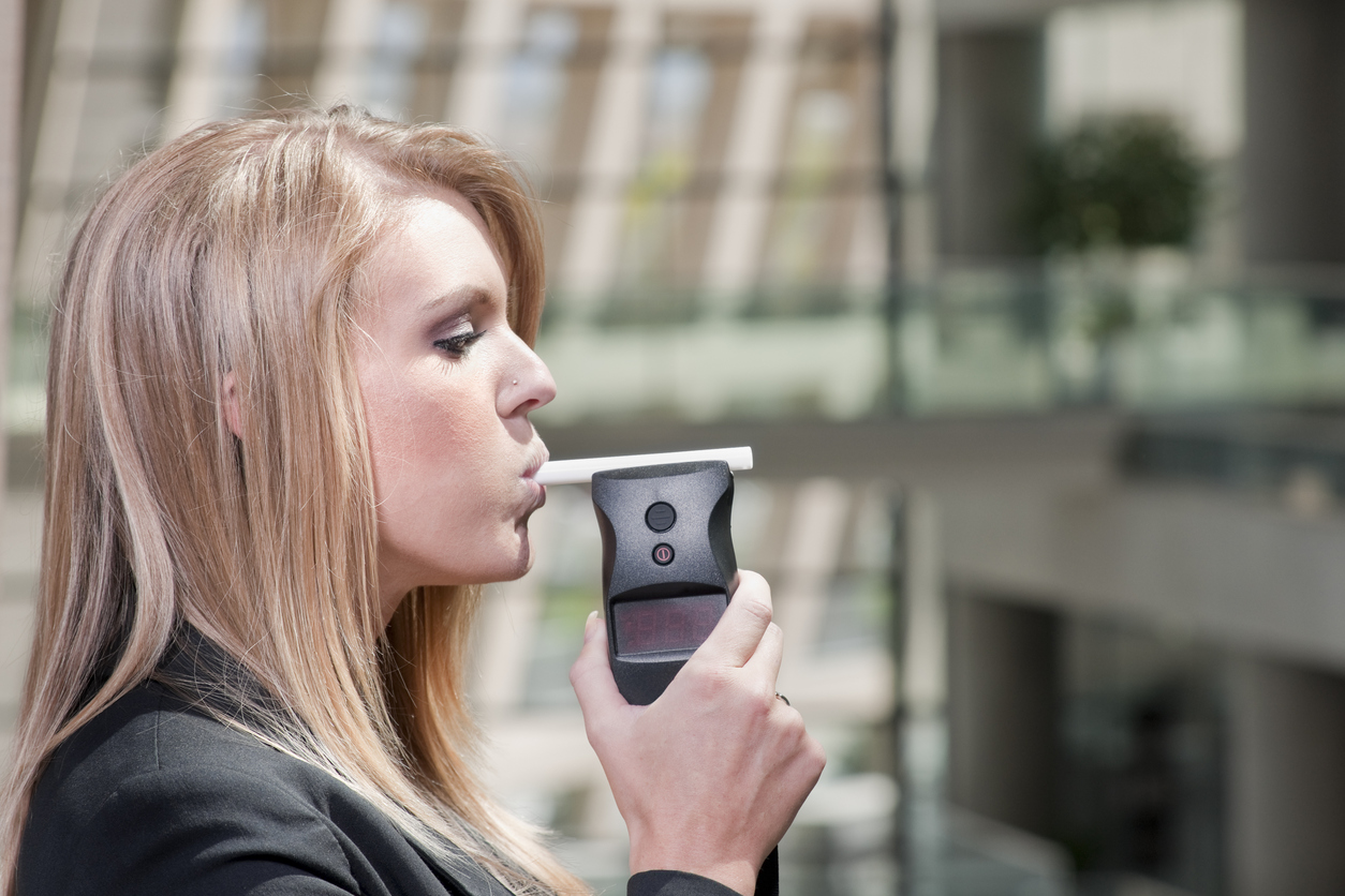 Stockphoto of a female using a breath alcohol testind device.