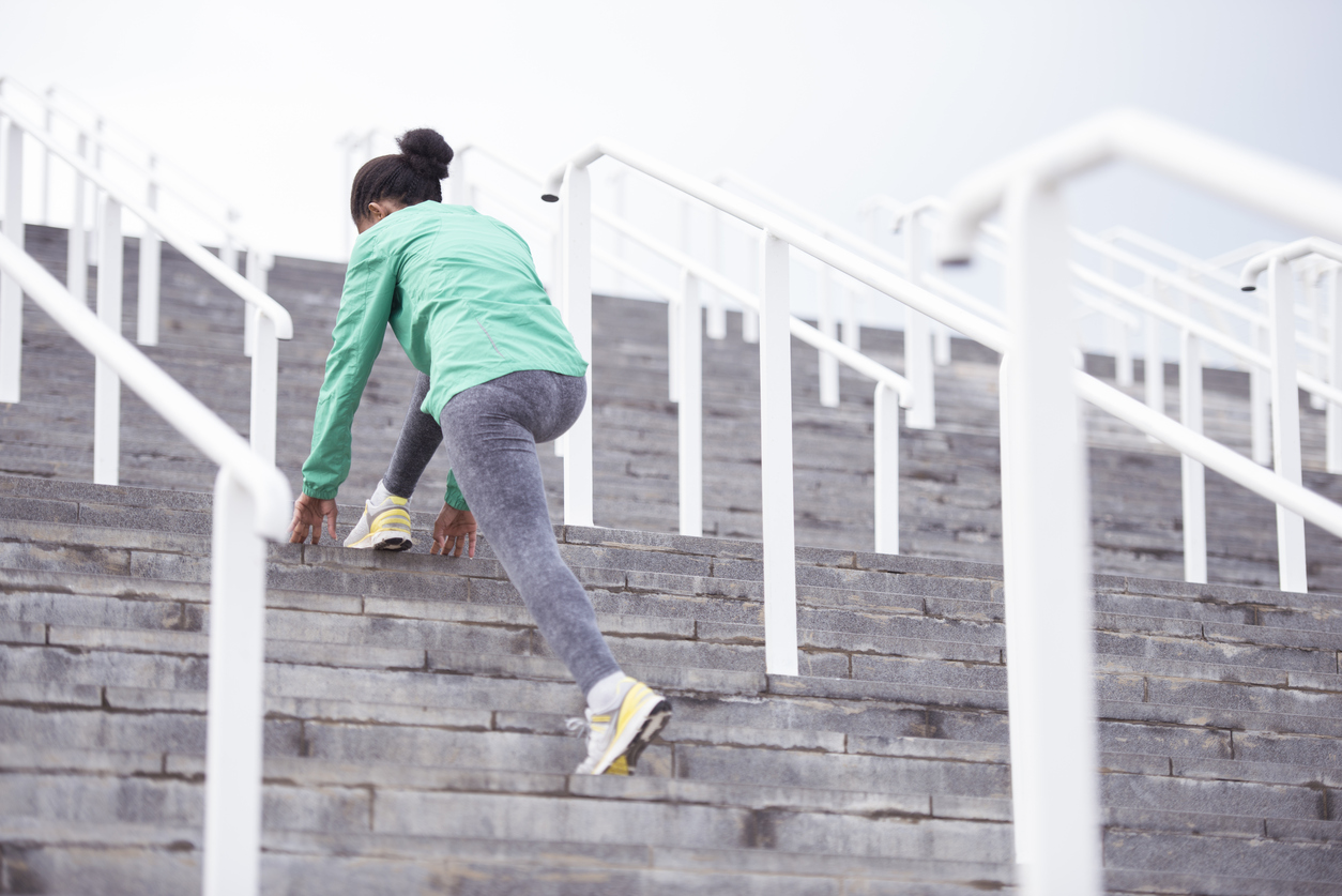 Photo from below of young woman wearing green sport jacket and gray tights, stretching her legs at stadium stairs early in the morning. Fitness, diet, active lifestyle concept.