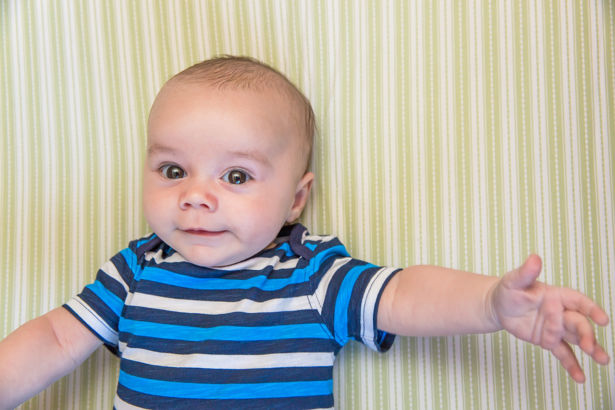 Close-up of a baby boy (two and a half months old) laying in his crib on a green and white striped sheet looking up. The camera is directly above him. The baby is wearing a blue and white striped short sleeve shirt and has a small smile on his face.