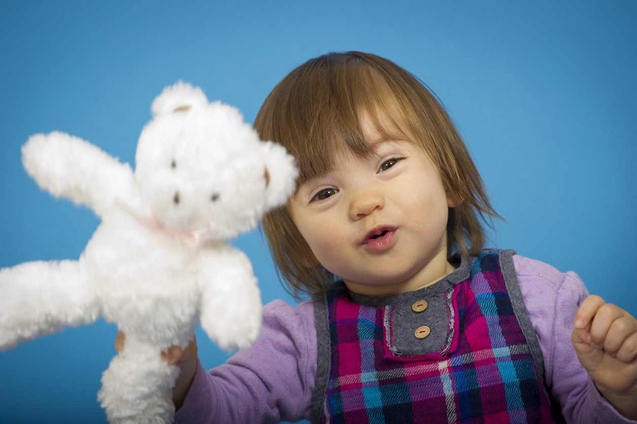 One year old girl holding a stuffed bear in the foreground and looking to camera