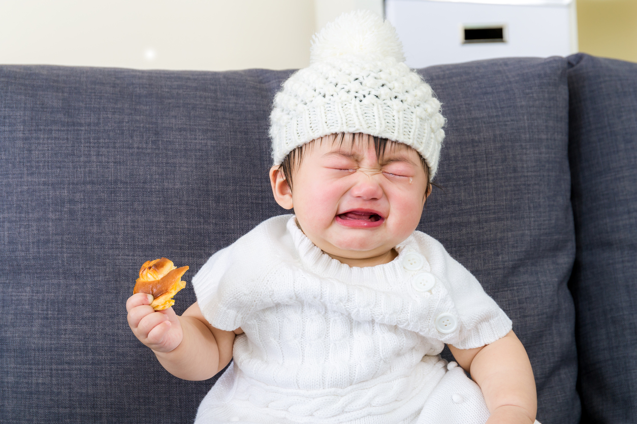 Little girl crying with bread holding on hand