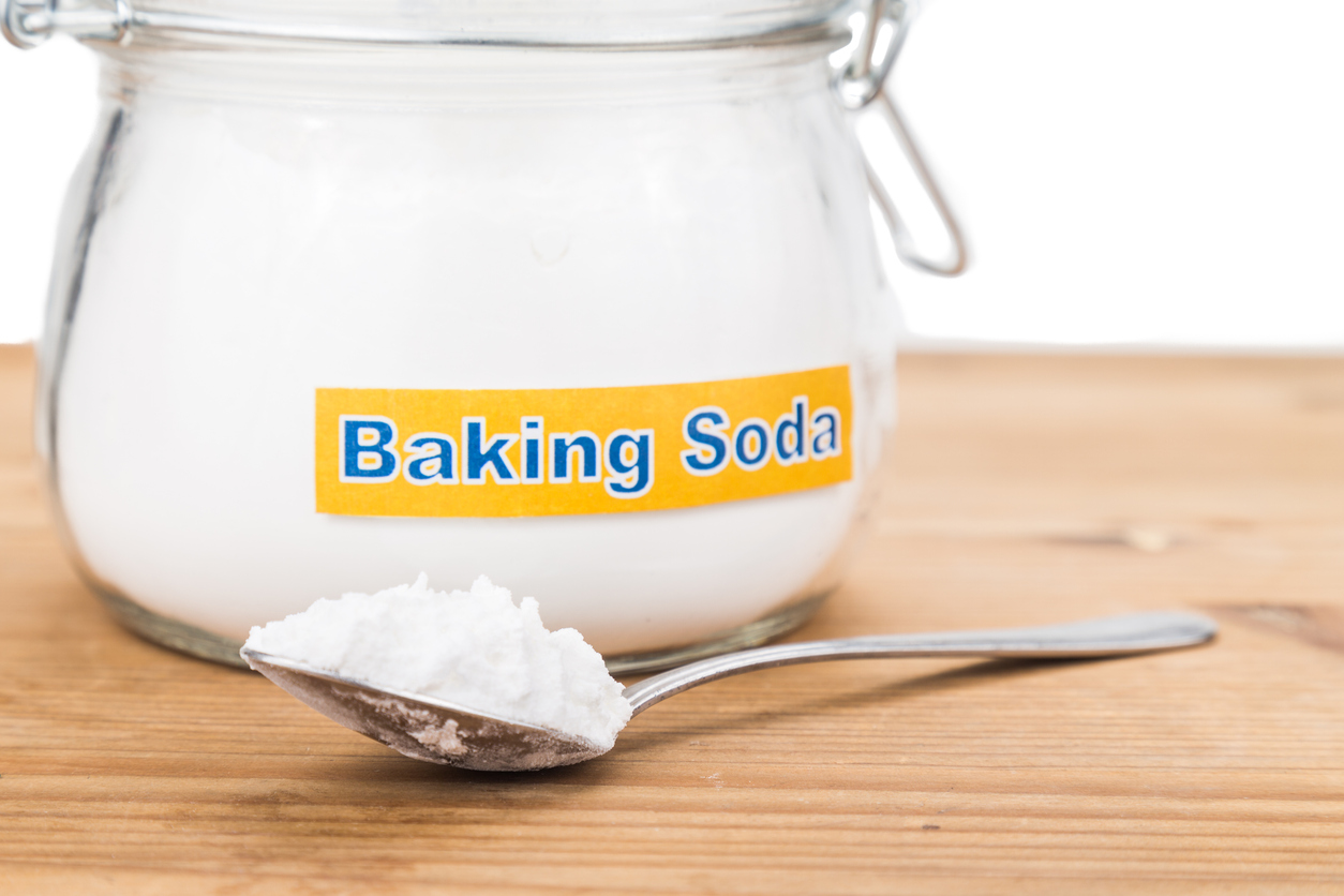Jar and spoonful of baking soda for multiple holistic usages.