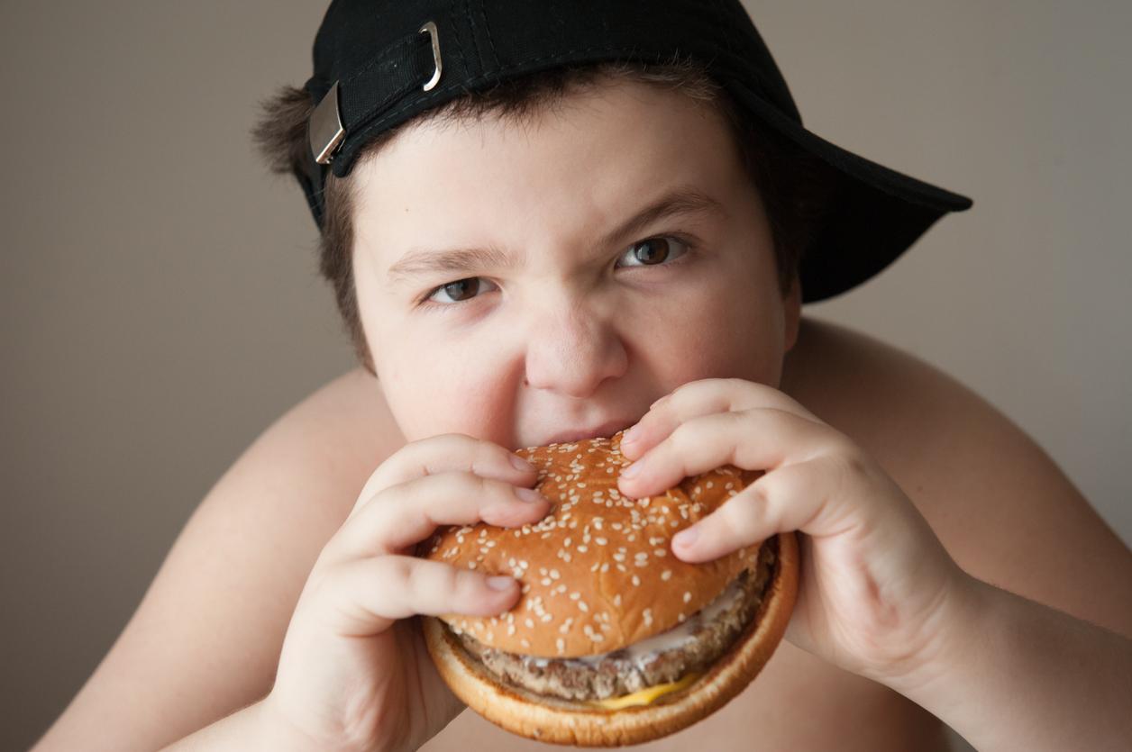 fat boy in cap eats a hamburger