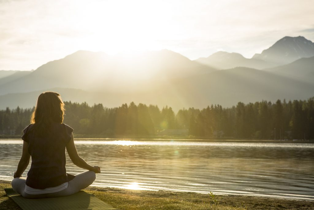 Meditation and yoga practice by lake at sunset or sunrise.