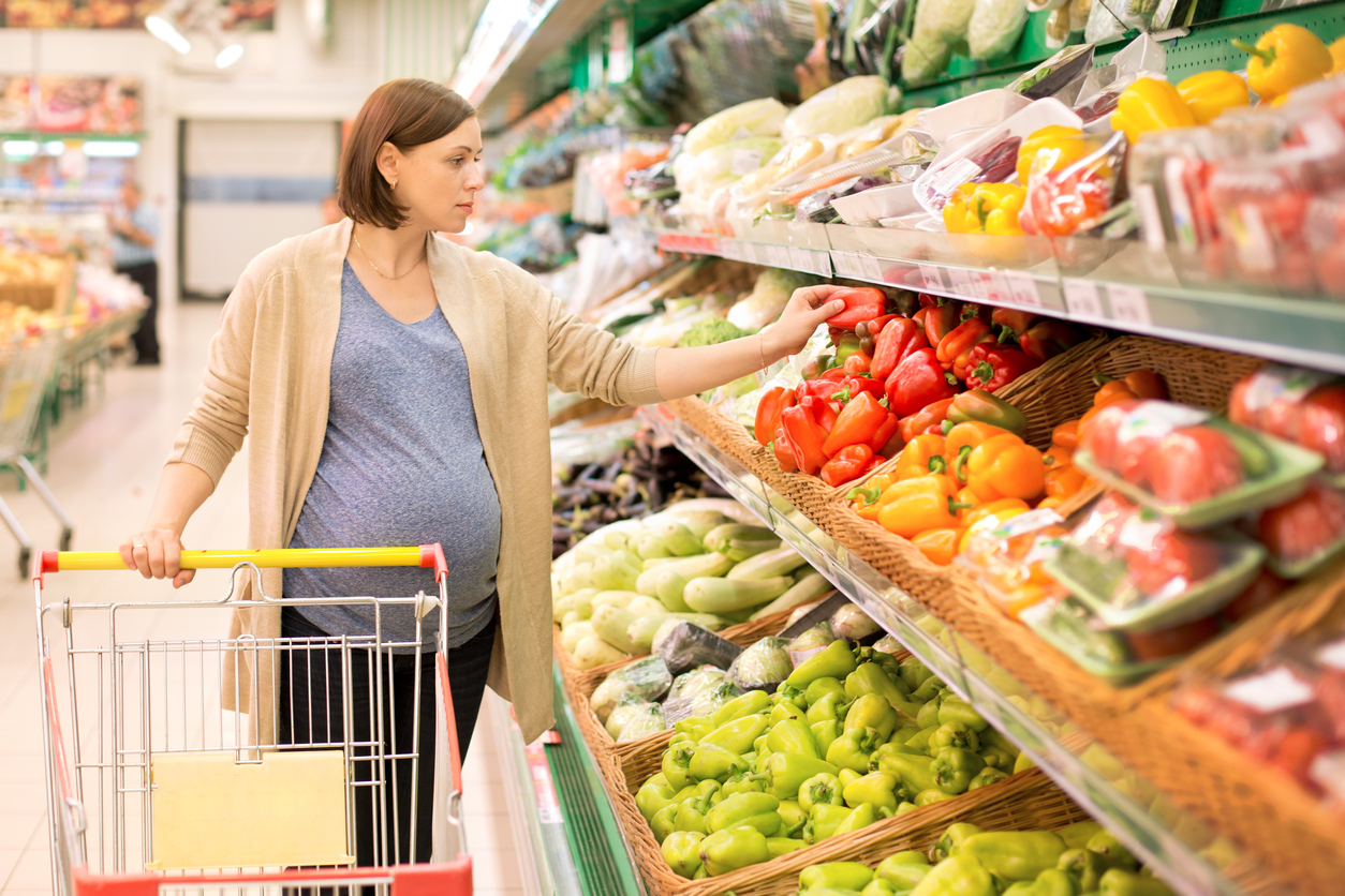 pregnant woman in a supermarket considering vegetables