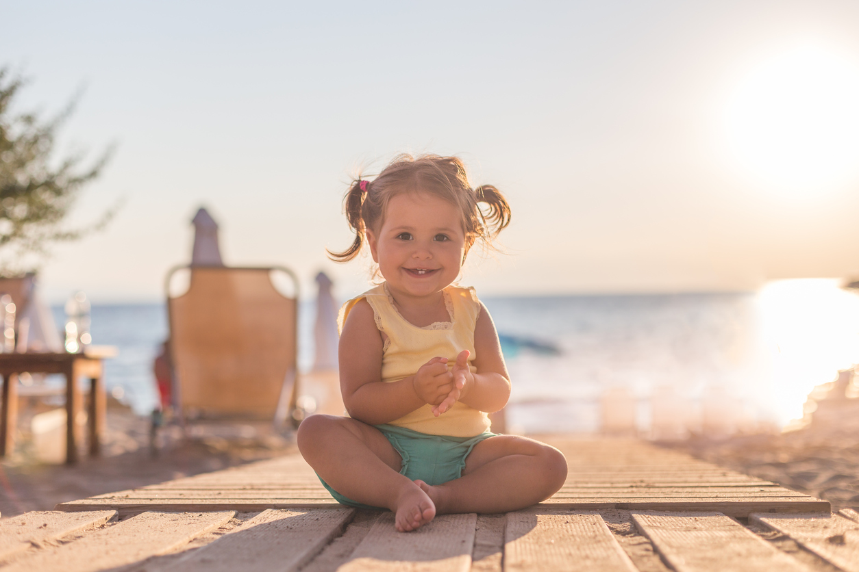 18 months old baby sitting and enjoying the sun , relaxing on a wooden boardwalk and discovering , happy baby - smiling and laughing