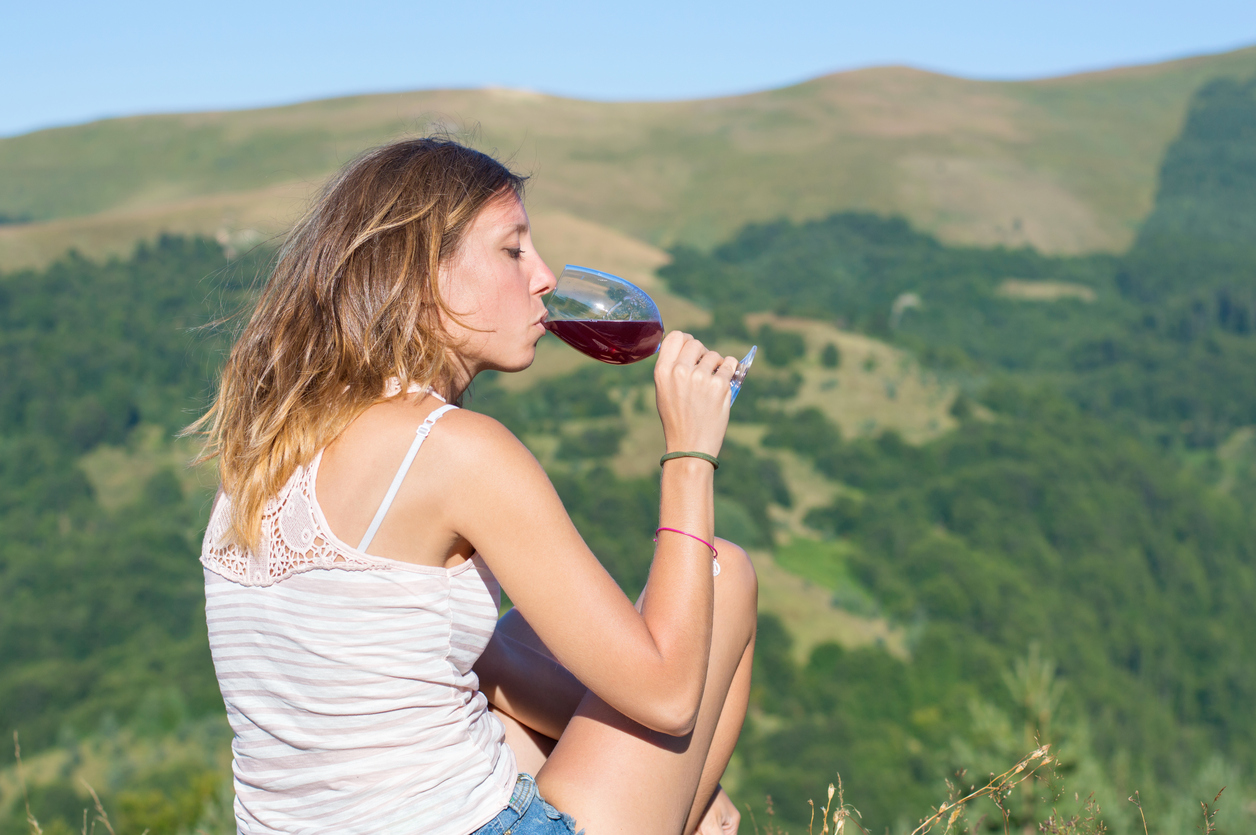 Girl drinking winewhile on a hiking trip picnic