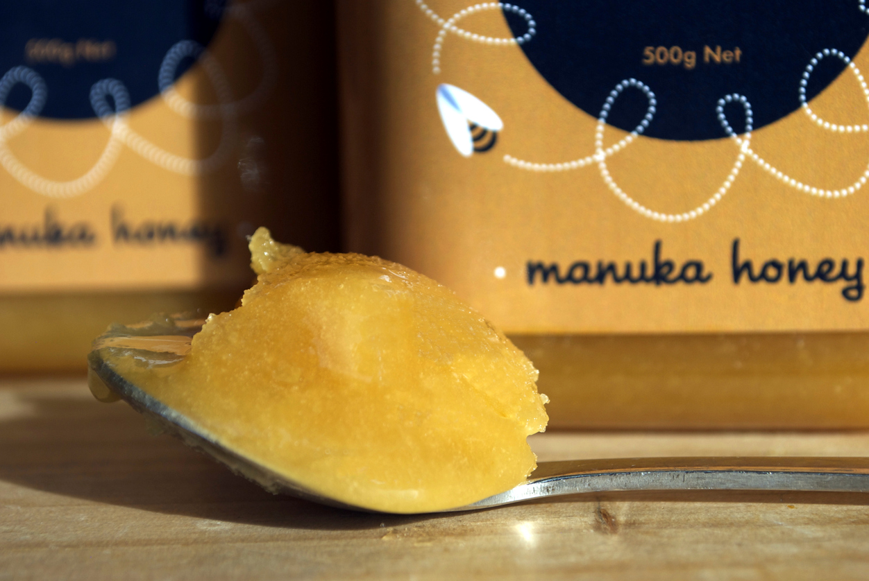 Motueka, New Zealand – August 15, 2014. Close-up of a spoonful of Manuka Honey. Out of focus are Manuka Honey jars, a product of the New Zealand company Moutere Beekeeping Ltd.