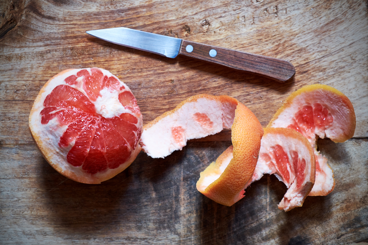 An old-fashioned wooden-handled paring knife sits on a chopping board next to a peeled pink grapefruit.