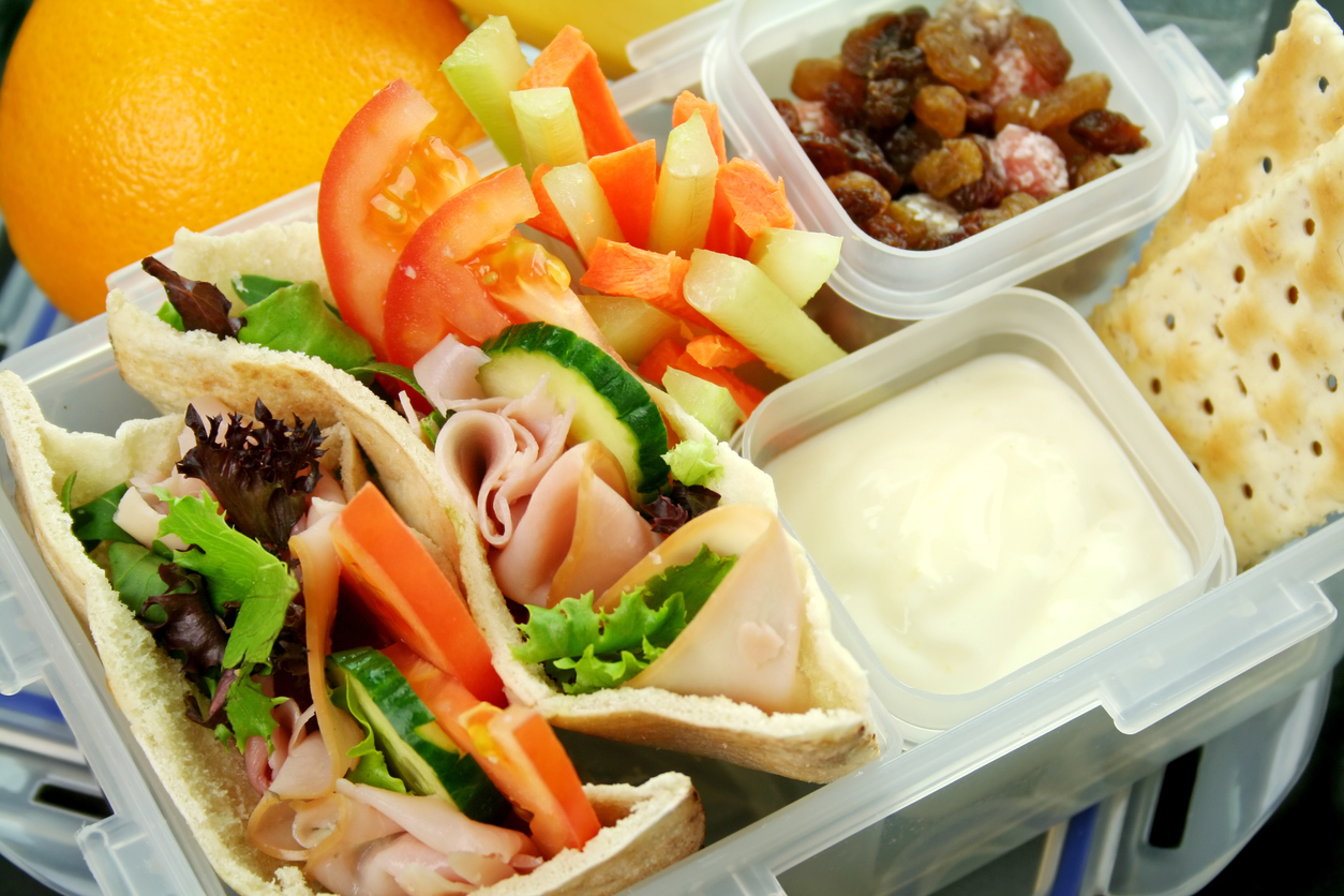 Healthy kid's lunch box made up of pita bread ham and salad, fresh fruit, sultanas and drinking water.
