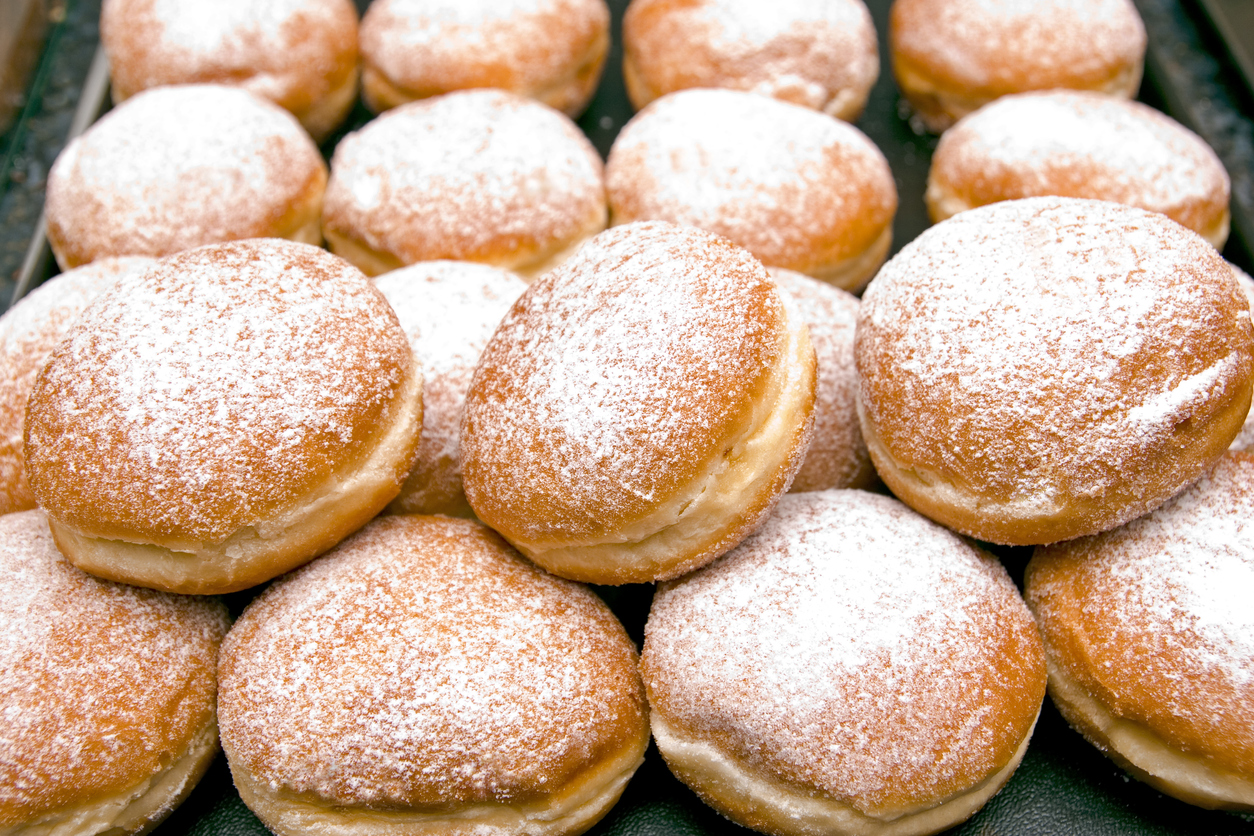 """""""Fresh baked German Jelly Doughnuts filled with strawberry jam or raspberry jam and dusted with powdered sugar. Full tray in a bakery counter display, delicious. Selective focus in foreground."""""""