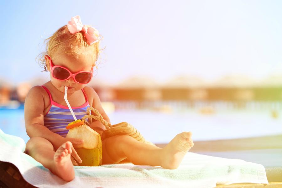 little girl drinking coconut cocktail on beach resort